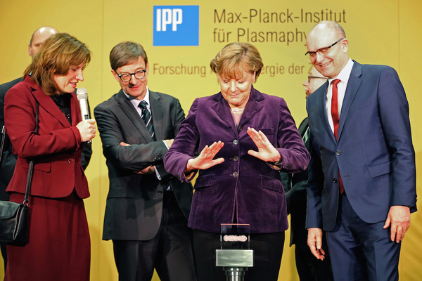 German chancellor Angela Merkel prepares to press the start bottom next to the head of the Max Planck Institute for Plasma Physics Sibylle Guenter, left, and Mecklenburg-Western Pomerania governor, Erwin Sellering, right at the Wendelstein 7-X' nuclear fusion research center at the Max-Planck-Institut for Plasma Physics in Greifswald, Germany Wednesday Feb. 3, 2016. (Bernd Wuestneck/AP)