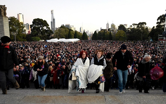 At Melbourne's Shrine of Remembrance thousands of people walked up the stairs at the end of the service to lay poppies. - AAP