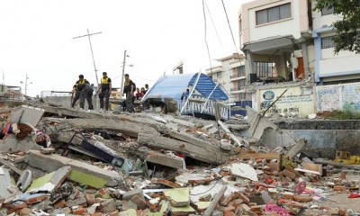 Police officers stand on debris in Tarqui neighborhood in Manta. Photo: Guillermo Granja/Reuters