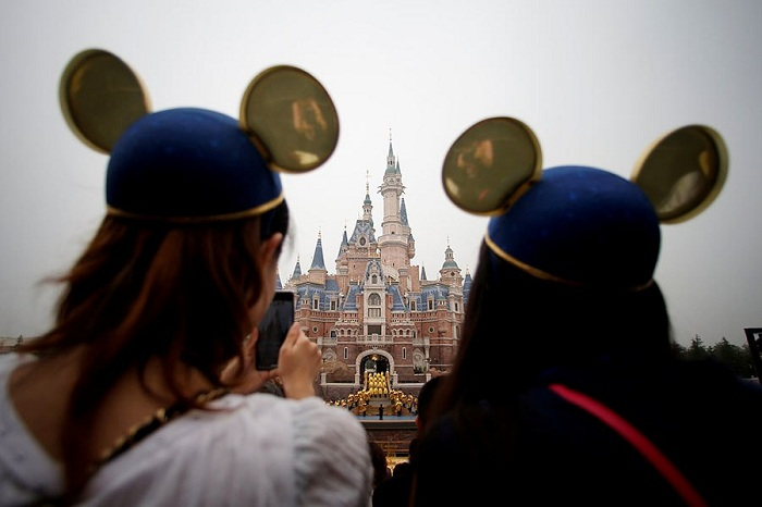 Women wearing Mickey Mouse ears watch the opening ceremony at Shanghai Disney Resort in Shanghai, China
