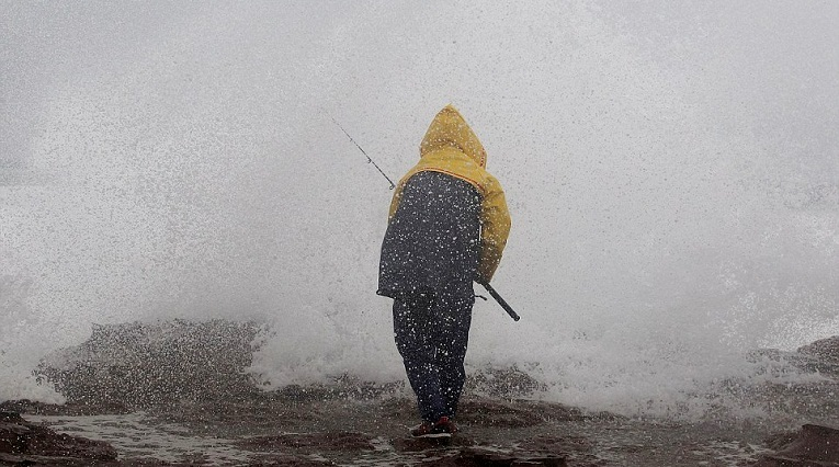 A fisherman at North Avoca Beach on the New South Wales Central Coast braves the wild weather conditions on Saturday