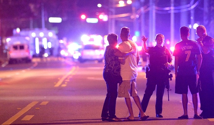Police direct relatives away from the scene of a mass shooting at a gay nightclub in Orlando, Fla., early Sunday. (AP Photo/Phelan M. Ebenhack)