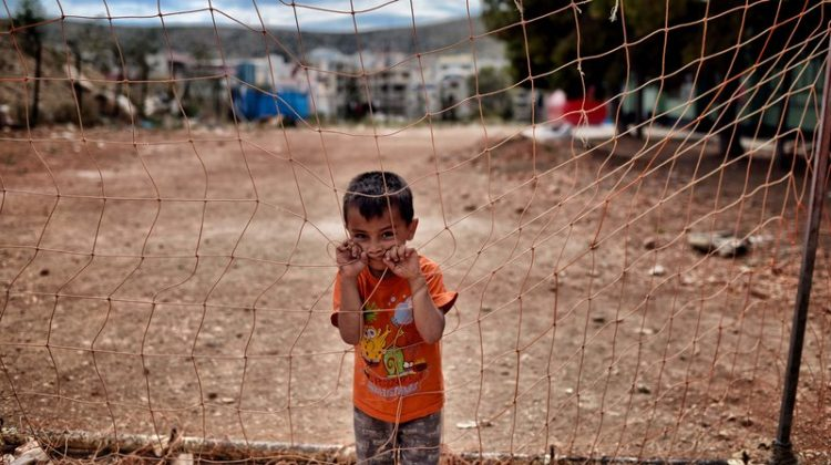 A boy looks on behind a net at the refugee camp of Schisto in Athens, Greece, on June 8. Photo: Aris Messinis/AFP/Getty Images