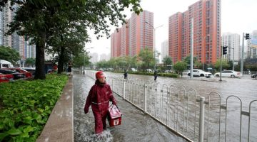 A food deliveryman wades through a flooded street during a heavy rainfall in Shilipu, Chaoyang Road, Beijing, China, July 20, 2016. Photo: REUTERS/Jason Lee