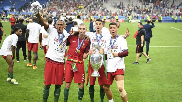Portugal's forward Eder (L), Portugal's defender Pepe, Portugal's defender Fonte pose with Portugal's forward Cristiano Ronaldo (R) as he holds the winners' trophy after beating France 1-0 in the Euro 2016 final football match between France and Portugal at the Stade de France in Saint-Denis, north of Paris, on July 10, 2016. / AFP / MARTIN BUREAU (Photo credit should read MARTIN BUREAU/AFP/Getty Images)