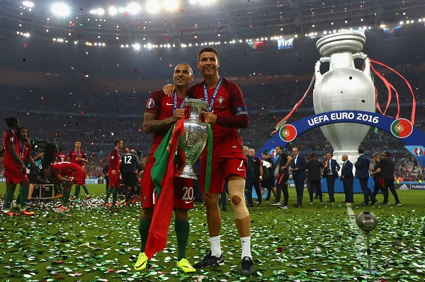 Portugal's forward Eder (L), Portugal's defender Pepe, Portugal's defender Fonte pose with Portugal's forward Cristiano Ronaldo (R) as he holds the winners' trophy after beating France 1-0 in the Euro 2016 final