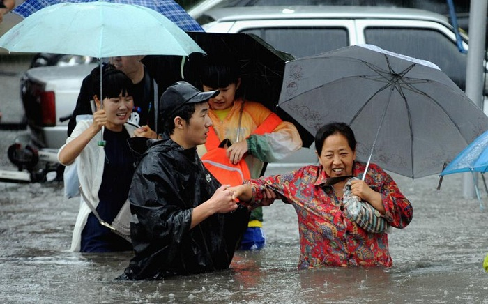 People walk through a flooded area during heavy rainfall in Beijing, China on July 20, 2016.