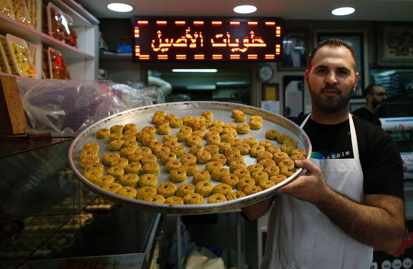 A Palestinian man shows traditional date-filled cookies at a bakery in Jerusalem's Old City on July 5, 2016, ahead of Eid-ul-Fitr. Photo: Ahmad Gharabali/AFP/Getty