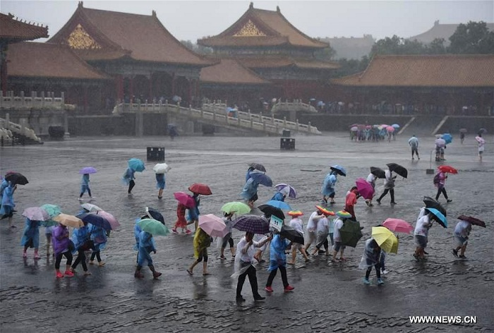 Tourists visit the Forbidden City in rain in Beijing, capital of China, July 20, 2016. Beijing's meteorological bureau issued an orange alert for rainstorm Wednesday noon. Photo: Xinhua/Luo Xiaoguang