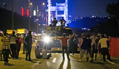 People stand in front of a tank near the Fatih Sultan Mehmet Bridge during clashes with military forces in Istanbul early on July 16. Photo: Gurcan Ozturk/AFP/Getty Images