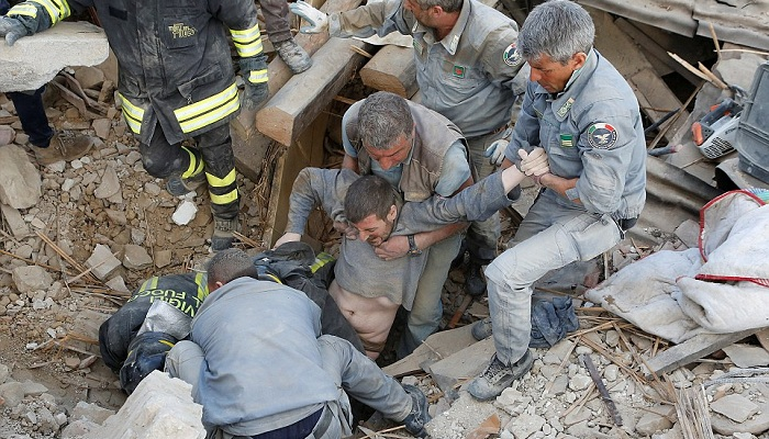 A dust-covered man trapped in the rubble of his home as he slept is pulled from a hole by rescuers in Amatrice this morning