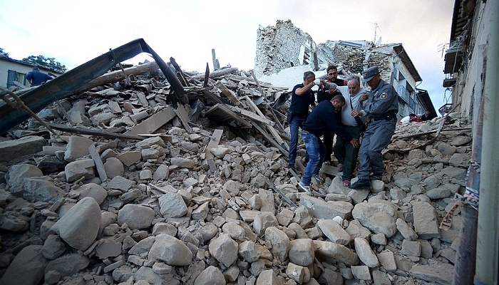 A survivor in Amatrice is helped to safety after a powerful earthquake has rocked Italy overnight killing at least 38 people and burying many more as they slept