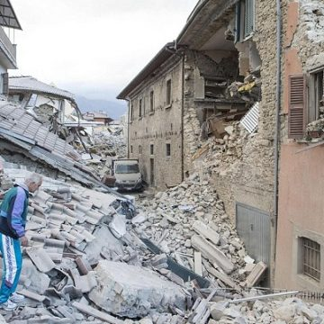 An elderly man in a tracksuit walks on the rubble of a collapsed buildings in Amatrice