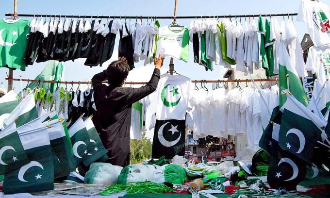 A vendor sells national flags of all shapes and sizes in Islamabad. Photo: APP