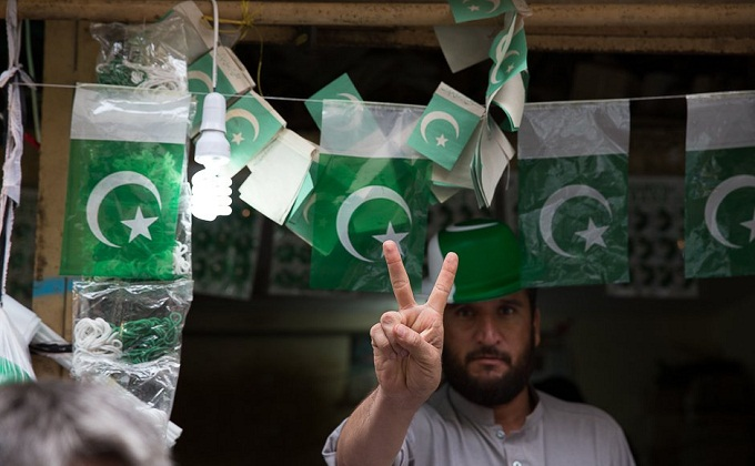 A flag seller poses with the victory sign as flags flutter around him. Photo: Zoral Naik