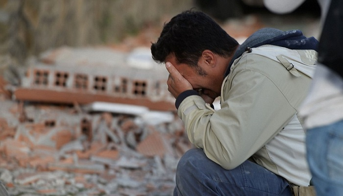 A dust-covered man cries with his head in his hands as the shock of what has happened overnight sinks in