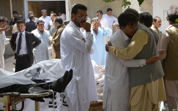 Relatives mourn next to bodies of victims after a bomb explosion at the Civil Hospital premises in Quetta on August 8, 2016. PHOTO: AFP