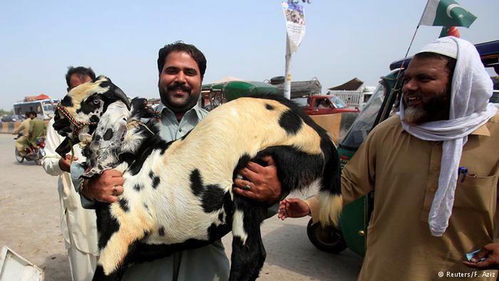 A man carries a goat for slaughter ahead of Eid in Peshawar, Pakistan