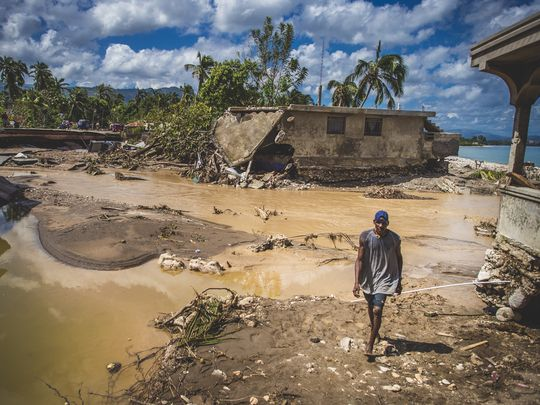 A man walks across flooded countryside in Nippes, Haiti. (Photo: Sean Sheridan, Mercy Corps)