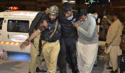 Rescuers help an injured person to a hospital in Quetta, Pakistan, after a hostel for police cadets was attacked by militants. Photo: Arshad Butt/AP