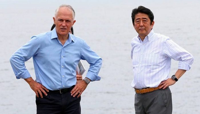 Prime Minister Shinzo Abe and Australian leader Malcolm Turnbull walk together along the shore of Sydney Harbor on Saturday. Photo: REUTERS