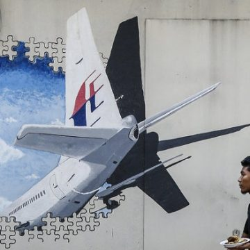 A waiter walks past a mural of Flight MH370 in Shah Alam outside Kuala Lumpur, Malaysia, in February 2016. The flight disappeared nearly three years ago with 239 people on board, and the search for the plane has now been suspended. Photo: Joshua Paul/AP