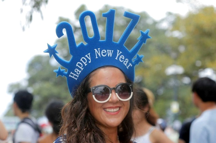 Chilean tourist Paula Aedo wears novelty headwear to usher in 2017 in Sydney. Photo: Reuters/Jason Reed