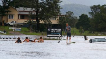 Local residents paddle down the main street on Friday in Billinudgel.