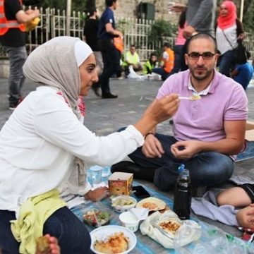 People eat their Iftar (breaking fast) meals while awaiting the call for prayers, after gathering through social networking sites, during the holy month of Ramadan in Amman July 27, 2013. Hundreds of Muslims gathered with prepared Iftar food, coordinating through social networking sites like Facebook and Twitter. REUTERS/Muhammad Hamed (JORDAN - Tags: RELIGION SOCIETY)