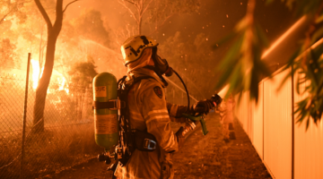 A firefighter hoses down an endangered home in southwest Sydney over the weekend. Photo: AAP